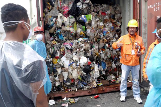 Philippine customs officials inspect cargo containers containing tonnes of garbage shipped by Canada at Manila port November 10, 2014. Picture taken November 10, 2014. Mandatory credit BAN Toxics/Handout via REUTERS