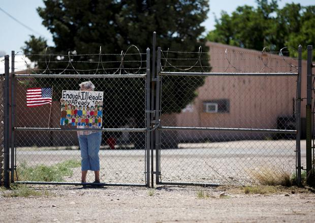 On the fence: A supporter of Trump's migrant policy holds a placard on the border. Photo: REUTERS/Adria Malcolm