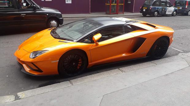 TRANSPORTS OF DELIGHT: An orange Lamborghini complete with custom plates parked near the UK Houses of Parliament