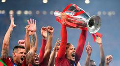Liverpool's Dutch defender Virgil van Dijk raises the European Champion Clubs' Cup as he celebrates with teammates winning the UEFA Champions League final football match between Liverpool and Tottenham Hotspur at the Wanda Metropolitano Stadium in Madrid. (Photo by GABRIEL BOUYS / AFP)GABRIEL BOUYS/AFP/Getty Images