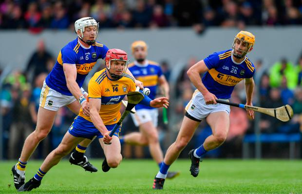 Clare's John Conlon of Clare is fouled by Pádraic Maher of Tipperary, left, as team-mate Barry Heffernan looks on during the Munster SHC Round 3 match in Ennis, Co Clare. Photo: Piaras Ó Mídheach/Sportsfile