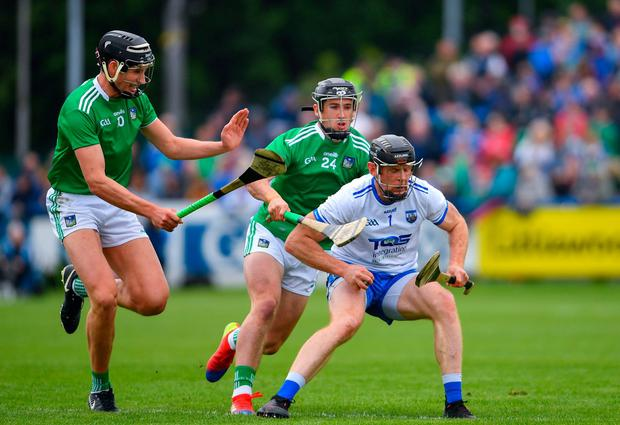 Kevin Moran of Waterford in action against Gearoid Hegarty, left, and Darragh O'Donovan of Limerick. Photo: Ramsey Cardy/Sportsfile