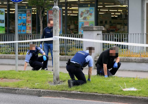 Seeking evidence: Gardaí conduct a fingertip search at the scene of the shooting near Lidl on the Blakestown Road in Mulhuddart. Photo: Frank McGrath