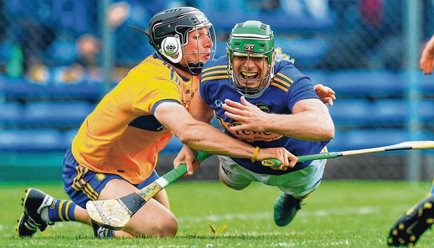 Tipperary's John O'Dwyer gets the handpass away as he's challenged by Clare's David McInerney during yesterday's Munster SHC clash at Cusack Park, Ennis. Photo: Piaras Ó Mídheach/Sportsfile