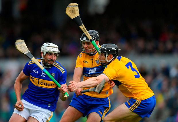 Patrick Maher of Tipperary in action against Cathal Malone, centre, and David McInerney of Clare. Photo: Piaras Ó Mídheach/Sportsfile