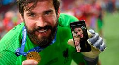 Liverpool goalkeeper Alisson celebrates on the pitch with his Champions League medal while speaking with his wife and daughter on a video call. Photo: Matthias Hangst/Getty Images