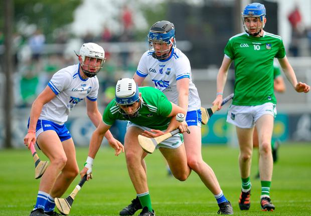 Ethan Hurley of Limerick in action against Tristan Loftus of Waterford. Photo: Ramsey Cardy/Sportsfile