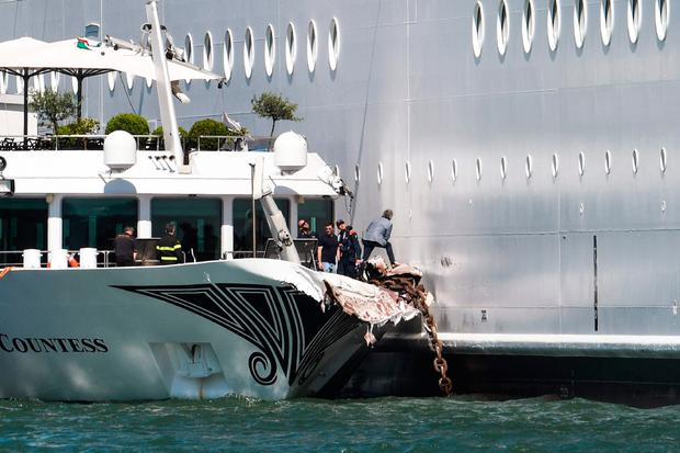Lucky escape: Engineers look at the damaged River Countess tourist boat alongside the MSC Opera cruise ship, which struck it. Photo: ANDREA PATTARO/AFP/Getty Images