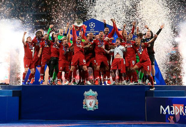 Liverpool's Jordan Henderson lifts the trophy with his team-mates