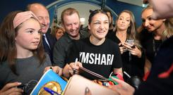 Katie Taylor signs some autographs for fans after she arrived into Dublin airport. Photo: Frank McGrath