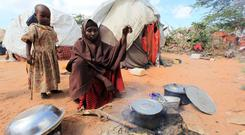 A woman cooks food for her children in a camp set up for internally displaced people in Dinsoor in southern Somalia