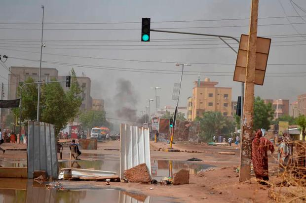 Smoke rises behind barricades laid by protesters to block a street in the Sudanese capital Khartoum to stop military vehicles from driving through the area. Photo: Mohammed Najib via AP