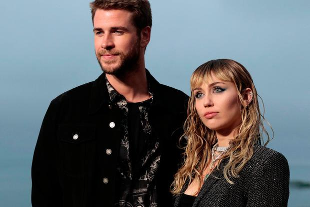 US singer Miley Cyrus and husband Australian actor Liam Hemsworth arrive for the Saint Laurent Men's Spring-Summer 2020 runway show in Malibu, California, on June 6, 2019. (Photo by Kyle GRILLOT / AFP)