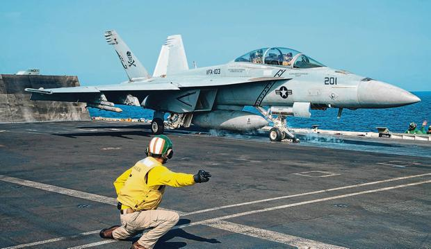 Taking off: A crew member signals as a pilot in an F/A-18 fighter jet is launched off the deck of the USS Abraham Lincoln in the Arabian Sea. Photo: AP/Jon Gambrell