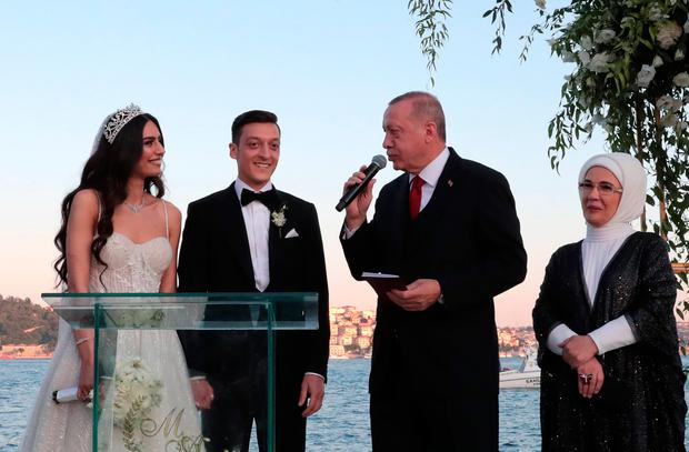 A handout photo released by the Turkish president's press office shows Arsenal's German midfielder Mesut Ozil (C-L) and his fiance Amine Gulse (L) standing next to Turkish President Recep Tayyip Erdogan (C-R) and his wife Emine during their wedding ceremony at the Four Seasons Bosphorus Hotel in Istanbul, Turkey