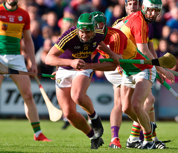 Wexford's Conor McDonald surges ahead of Carlow's David English. Photo: Sportsfile