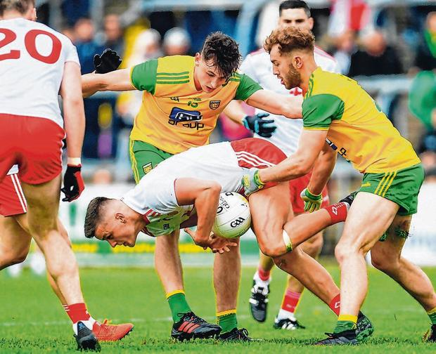 Darren McCurry of Tyrone has little room to manoeuvre as he's closed down by a Donegal pair of Michael Langan (left) and Stephen McMenamin on Saturday. Photo: Ramsey Cardy/Sportsfile