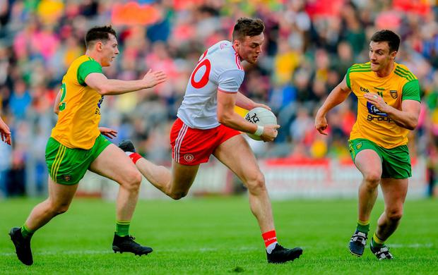 Brian Kennedy of Tyrone in action against Jamie Brennan, left, and Leo McLoone of Donegal. Photo: Ramsey Cardy/Sportsfile