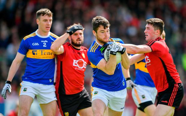Shane O'Connell of Tipperary is tackled by Conor Francis of Down. Photo: David Fitzgerald/Sportsfile