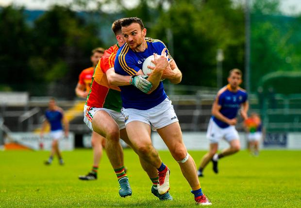 Donal McElligott of Longford in action against Josh Moore of Carlow. Photo: Ramsey Cardy/Sportsfile