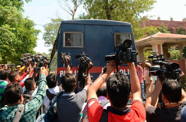 Furore: Media gather by a police van carrying the seven accused. Photo: NARINDER NANU/AFP/Getty Images