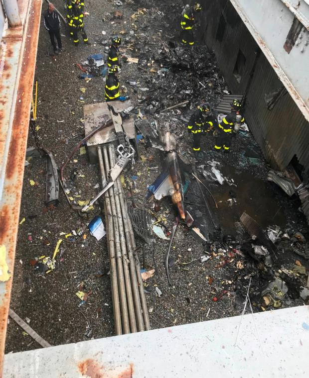 In this photo released on the Fire Department of New York (FDNY) twitter account, firefighters work on the scene of a helicopter that crash-landed on top of a high-rise in midtown Manhattan in New York on June 10, 2019 Credit: AFP PHOTO / Fire Department of New York