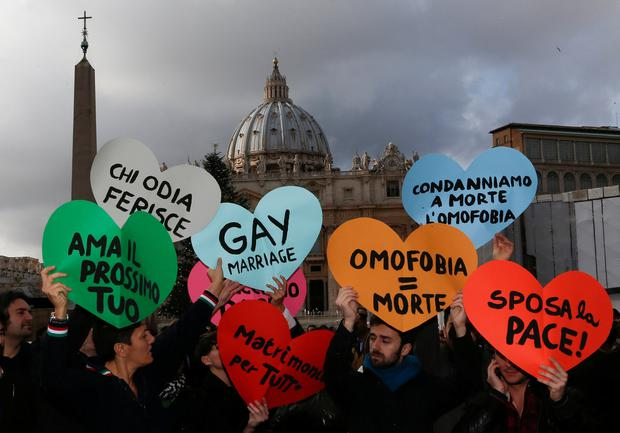 Members of a gay activist group hold signs in front of St. Peter's Square in the Vatican. REUTERS/Alessandro Bianchi/File Photo