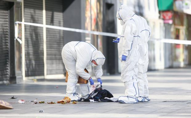 Evidence: Forensics officers examine items at the scene. Photo: Gerry Mooney