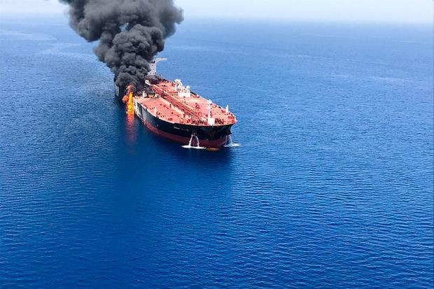 Mystery: An oil tanker billows flames and smoke after it was attacked at the Gulf of Oman by an unknown enemy. Photo: Reuters