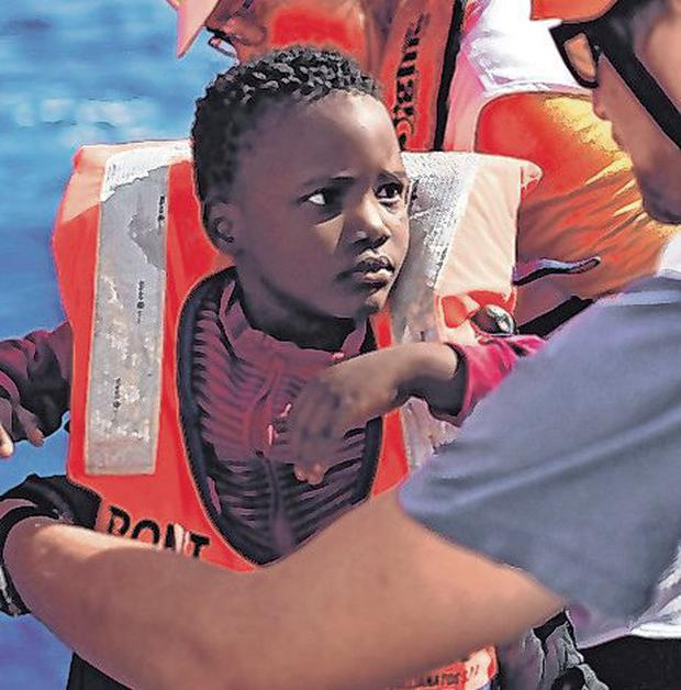 A migrant boy is helped in the Mediterranean by MSF. Photo: Gabriel Bouys/AFP/Getty Images