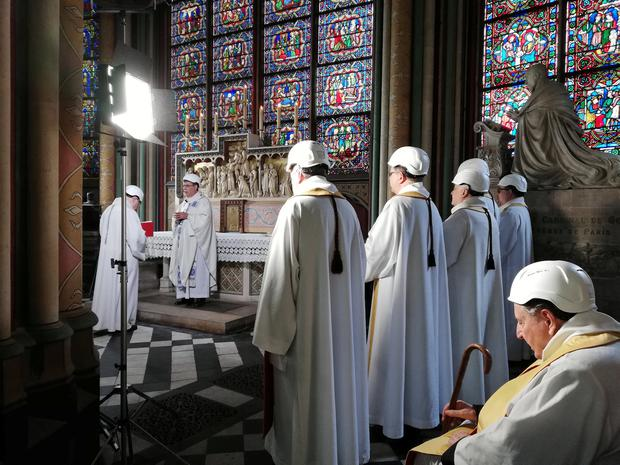 Hard hats: Archbishop of Paris Michel Aupetit leads the first mass in Notre-Dame, two months to the day after the fire. Photo: Karine Perret/Pool via REUTERS