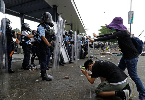 Clash: A protester bows to riot police after they fire tear gas towards protesters outside the Legislative Council in Hong Kong last Wednesday. Photo: AP Photo/Vincent Yu