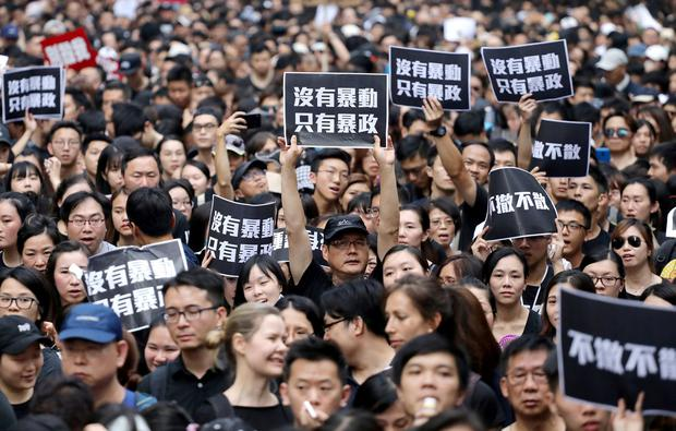 Protesters hold placards as they attend a demonstration demanding Hong Kong's leaders to step down and withdraw the extradition bill, in Hong Kong, China, June 16, 2019. REUTERS/Athit Perawongmetha