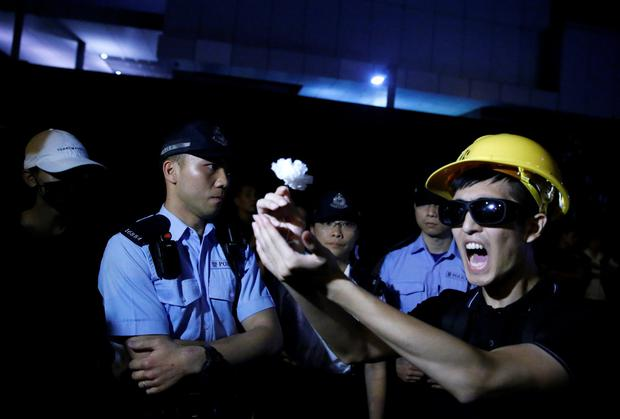 Peace: A protester offers a white flower to police officers during a rally attended by huge numbers demanding Hong Kong's leaders step down. Photo: REUTERS/Thomas Peter