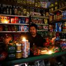 Outage: A shopkeeper waits for customers in candlelight in Buenos Aires. Photo: REUTERS/Agustin Marcarian