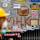 People walk past a wall covered in messages and posters in Hong Kong