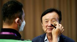 A staff member applies makeup for Huawei founder Ren Zhengfei before a panel discussion at the company headquarters in Shenzhen, Guangdong province REUTERS/Aly Song