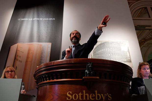 An auctioneer (C) gestures during an auction sale at Sotheby's action house in Paris. Photo: AFP/Getty Images