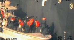 A U.S. military image released by the Pentagon in Washington on June 17, which is says was taken from a U.S. Navy MH-60R helicopter in the Gulf of Oman in waters between Gulf Arab states and Iran on June 13, shows personnel that the Pentagon says are members of the Islamic Revolutionary Guard Corps Navy removing an unexploded limpet mine from the M/T Kokuka Courageous. Photo: Reuters