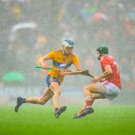 Diarmuid Ryan of Clare in action against Mark Coleman of Cork during a deluge of rain at the Munster GAA Hurling Senior Championship Round 5 match at Cusack Park in Ennis, Clare. Photo: Eóin Noonan/Sportsfile