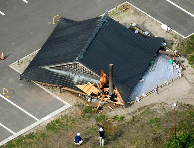 The roof of the wooden sumo building falls on the site of the Oizumi Elementary School in Tsuruoka, Yamagata prefecture Photo: Kyodo News via AP