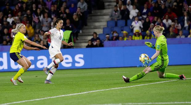 Sweden goalkeeper Hedvig Lindahl, right, blocks shot from United States' Carli Lloyd, centre, during the Women's World Cup Group F match in Le Havre, France.