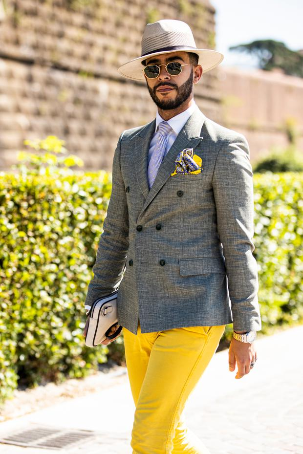 A guest, wearing a grey blazer, white shirt, white necktie, yellow pants, beige shoes, beige hat and white bag, is seen during Pitti Immagine Uomo 96 on June 13, 2019 in Florence, Italy. (Photo by Claudio Lavenia/Getty Images)