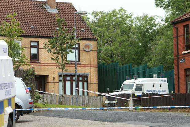 Police land rovers and white tape cordon off an area of Woodside Drive in Poleglass in Dunmurry Photo by Paul McErlane for the Belfast Telegraph