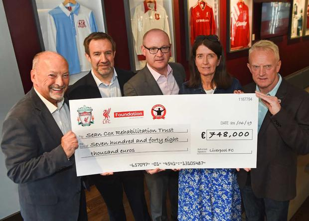 Martina Cox, wife of Sean Cox, accepts a cheque from Liverpool FC.