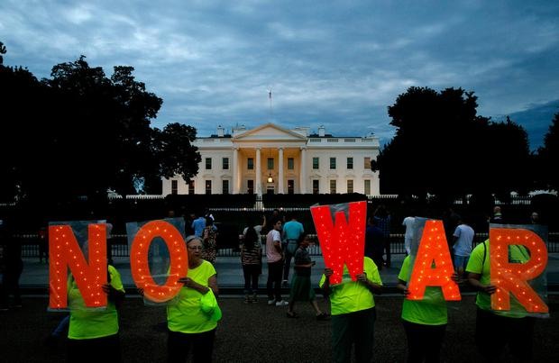 Fears: Protesters hold signs spelling out 'No War' outside the White House in Washington. Photo: AP/Jacquelyn Martin