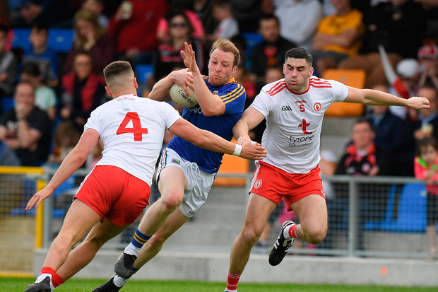 Padraig McCormack of Longford is tackled by Michael McKernan, left, and Michael Cassidy of Tyrone