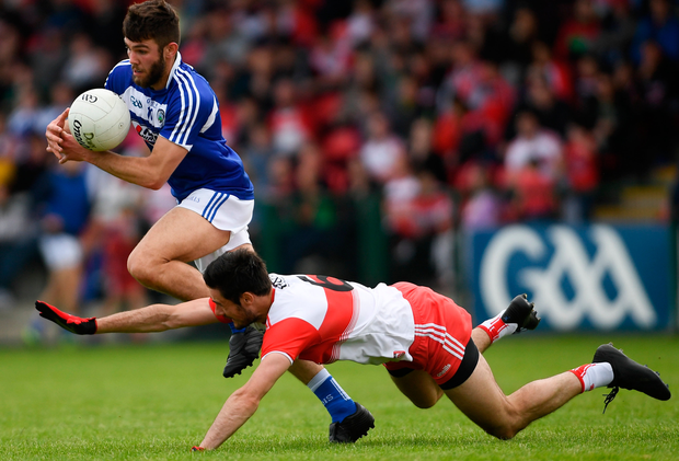 Laois' Daniel O'Reilly does his best to evade Derry's Chrissy McKaigue. Photo: Sportsfile