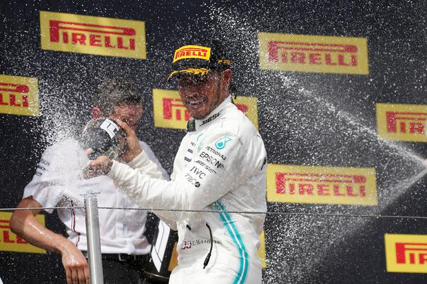 Mercedes' Lewis Hamilton celebrates with sparkling wine on the podium after winning the 2019 French Grand Prix. REUTERS/Vincent Kessler