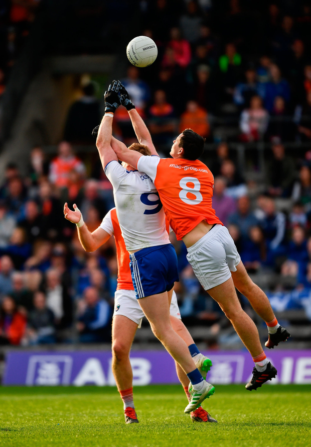 Kieran Hughes of Monaghan jumps with Armagh players Aaron Forker, 8, and Brendan Donaghy in an effort to win possession. Photo by Ray McManus/Sportsfile